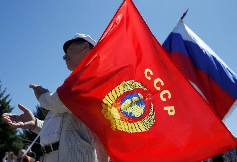A man holds a flag with the coat of arms of the Soviet Union and a Russian flag during a May Day rally in Stavropol